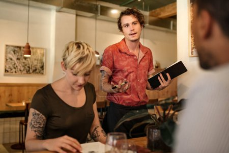 Young waiter talking with a group of customers reading menus at a table in a trendy bistro