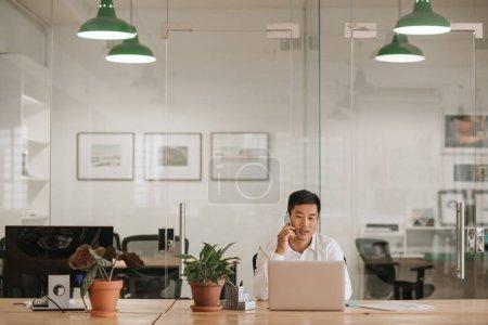 Jeune homme d'affaires asiatique assis seul à son bureau dans un bureau moderne travaillant sur un ordinateur portable et parlant sur un téléphone portable
