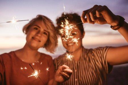 Photo pour Deux jeunes amies rire et jouer avec feux de Bengale, tout en ayant un bon moment ensemble à la plage au coucher du soleil - image libre de droit