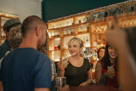 Photo pour Sourire de divers jeunes gens debout dans un trendy bar parler et rire ensemble plus de boissons - image libre de droit