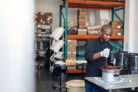 Photo pour Propriétaire d'une entreprise africaine dans une chocolaterie artisanale utilisant un sèche-cheveux pour garder le chocolat fondu dans un bol - image libre de droit