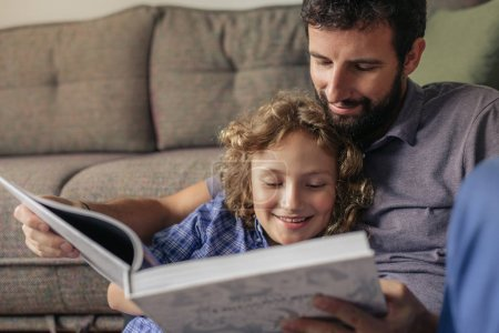 Photo for Single dad and his young son sitting together on their living room floor at home enjoying some quality time reading a book - Royalty Free Image