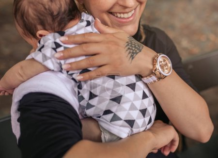 Photo for Closeup of a smiling young mother sitting outside on a bark bench cradling her adorable baby boy over her shoulder - Royalty Free Image