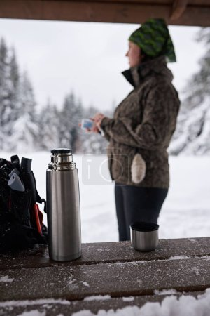 Young woman in hiking gear standing in a shelter drinking coffee while taking a break from a winter hike in a forest