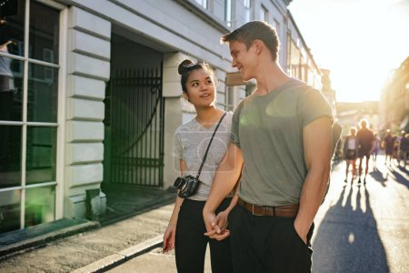 Photo for Smiling young couple talking together while walking hand in hand along a city street in the afternoon - Royalty Free Image