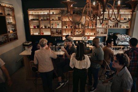 Foto de Gran ángulo de grupos de gente joven diversa disfrutando de bebidas durante una noche en un bar de moda - Imagen libre de derechos