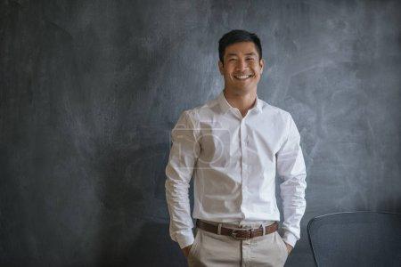 Photo pour Portrait d'un jeune homme d'affaires asiatique souriant debout les mains dans les poches devant un tableau blanc dans un bureau - image libre de droit