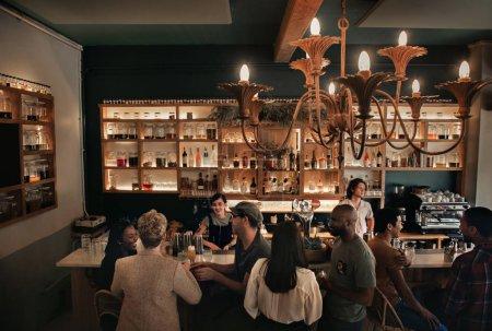 Foto de Alto ángulo de grupos de gente joven diversa que bebe y habla durante una noche en un bar - Imagen libre de derechos