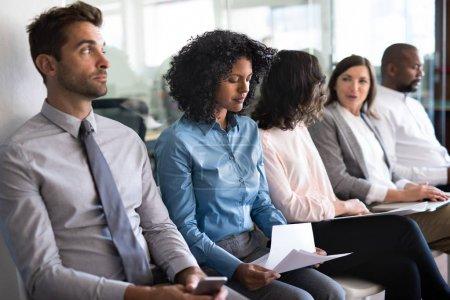 Photo pour Jeune femme passant en revue son curriculum vitae alors qu'elle est assise avec un groupe de demandeurs d'emploi en attente d'une entrevue - image libre de droit