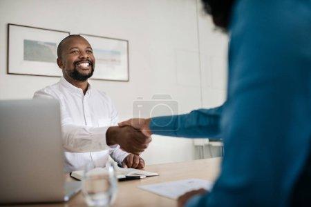 Photo pour Gestionnaire afro-américain souriant assis à son bureau serrant la main d'un demandeur d'emploi après une entrevue - image libre de droit