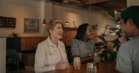 Young woman laughing while sitting at a table in a bar talking with a diverse group of friends over drinks