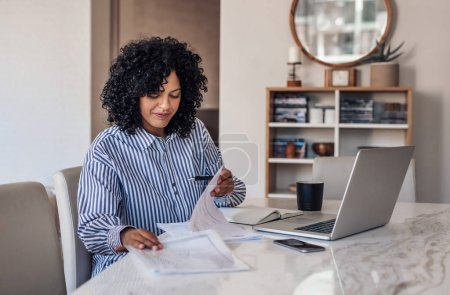 Photo for Smiling young female entrepreneur going through paperwork while working on a laptop at her dining room table at home - Royalty Free Image