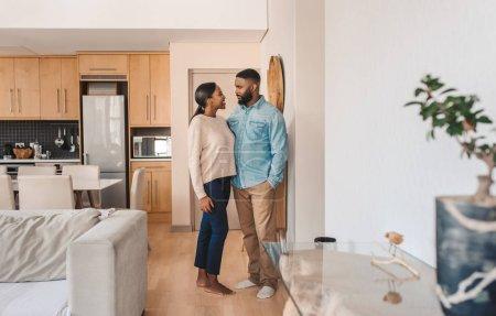Foto de Jóvenes afroamericanos se miran unos a otros y sonríen mientras se mantienen unidos en el brazo en un apartamento. - Imagen libre de derechos
