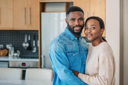 Photo pour Portrait d'un jeune couple afro-américain souriant debout bras dans le bras ensemble dans leur cuisine à la maison - image libre de droit