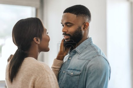 Photo pour Young African American man smiling and looking at his wife while standing arm in arm together in their modern apartment - image libre de droit