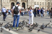 MILAN, ITALY - MAY 10, 2018: An unidentified couple tries to be photographed with pigeons on Cathedral Square.
