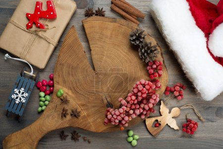 Photo pour Nouvel An et fond de Noël. Planche à découper, baies rouges, épices et assaisonnements, cônes et bonbons sur fond gris . - image libre de droit
