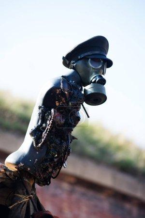 Photo pour Mannequin avec un capuchon et un masque à gaz. Décor dans le style de la post-apocalypse. Prise de vue extérieure, netteté sélective - image libre de droit