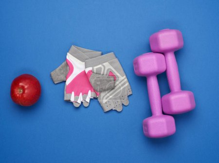 Sports gloves, a pair of purple dumbbells and a re...
