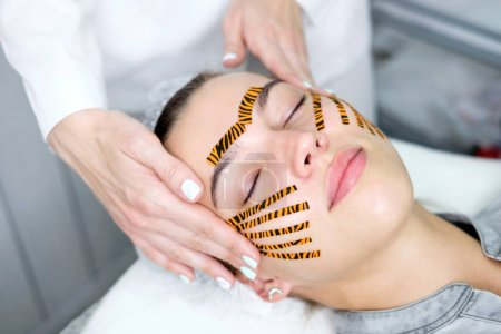 Cosmetologist making taping face procedure using tiger colored tapes in beauty parlor. Patient lying on the procedure table. Concept beauty.