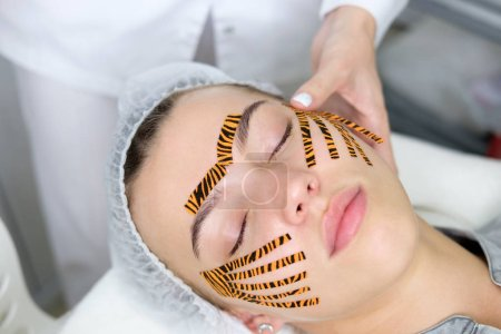 Cosmetologist making taping face procedure using tiger colored tapes in beauty parlor. Young attractive woman or model with closed eyes lying on the procedure table. Concept beauty.
