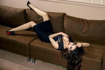 Photo pour Sexy jeune femme brune belle posant dans une robe noire - image libre de droit