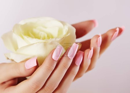 Elegant female hands with Pink Manicured Nails. Be...