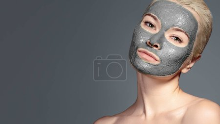 Photo pour Belle femme appliquant un masque facial noir. Soins de beauté. Gros plan Portrait d'une fille thermale Appliquer de l'argile Masque facial sur fond gris. - image libre de droit