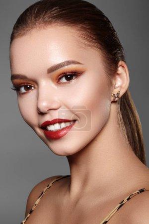 Photo pour Belle femme avec le maquillage professionnel. Party Gold Eye Make-up, Perfect Eyebrows, Shine Skin. Look de mode lumineux avec des lèvres rouges - image libre de droit