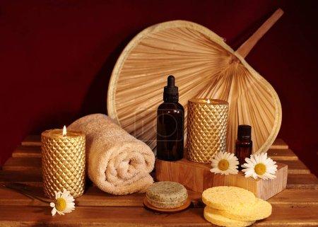 Photo pour Belle composition de spa. Aromathérapie avec huile à base de plantes, savon naturel et bougies d'or. Couleur de relaxation et serviettes de réchauffement sur le fond en bois - image libre de droit