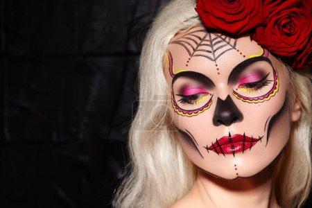 Photo pour Belle Halloween maquillage Style. Blonde modèle porter sucre crâne maquillage avec Roses rouges, pâle de tons de peau et de cheveux de vagues. Santa Muerte concept - image libre de droit
