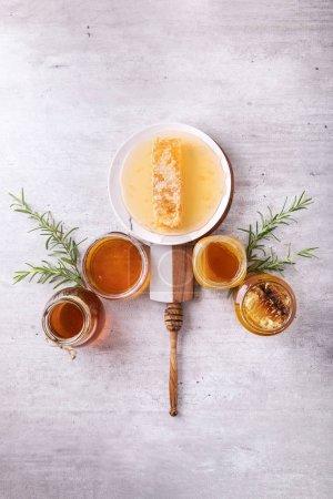 Photo pour Miel dans un bocal avec trempette au miel et nid d'abeille sur fond blanc. Vue du dessus - image libre de droit
