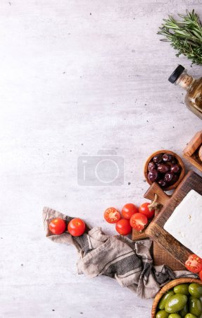 Photo for Traditional greek appetizer goat feta cheese served with fresh cherry tomatoes, herbs, green and black olives and extra virgin olive oil over a grey background. Top view. Copy space - Royalty Free Image