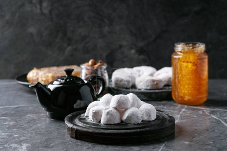 Photo for Variety of traditional Greek sweets cookies kourabiedes and akanes lukum in sugar powder served with honey, almonds and black tea over black texture background. - Royalty Free Image
