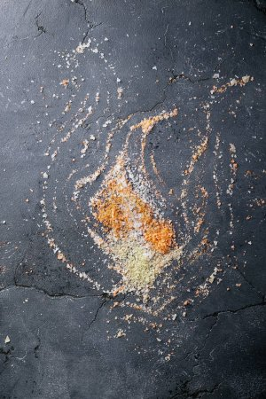 Photo pour Variété de sel et d'assaisonnement sur fond de texture noire. Vue de dessus, plan plat. Espace de copie - image libre de droit