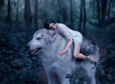 Photo pour Une fille fragile chevauchant un loup, comme la princesse Mononoke. Belle au bois dormant. Alaskan Malamute est comme un loup sauvage. Le fond est une forêt de contes de fées aux couleurs fraîches . - image libre de droit