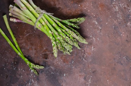 Photo pour Banquettes d'asperges vertes fraîches sur fond bois, vue de dessus - image libre de droit
