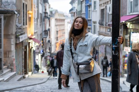 Photo pour A young girl  on the street of an old European city. Evening atmosphere, the lights are already included in the shops. - image libre de droit