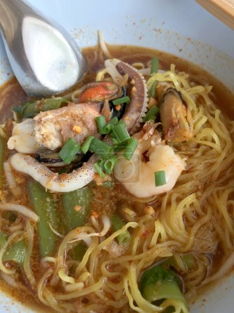 Delicious asian spicy seafood noodle soup with shrimp, squid and shellfish in white bowl on wooden table, Tom Yum Goong. Thai style food. vintage tone color filter.