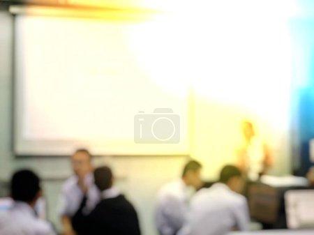 Concept d'éducation, Image de fond floue abstraite des étudiants et des gens d'affaires étudiant et discutant dans une grande salle séminaire de profession avec écran et projecteur pour montrer l'information .