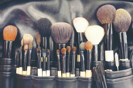 Photo pour Brosses de maquillage professionnelles cosmétiques en tube, sac en cuir. pinceau gros plan, outils de maquillage de, poudre, ensemble de différents objets pour maquilleur dans leur support. Ensemble de produits de maquillage arrangés - image libre de droit