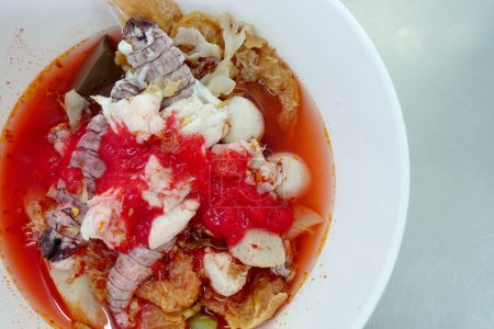Photo for Yentafo Spicy noodle soup,hot and spicy ,with mix seafood, crayfish, shrimp. Asian spicy seafood noodle soup in white bowl on table background. Thai style noodle and street food of Thailand. - Royalty Free Image