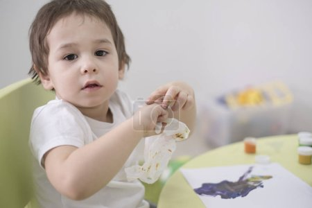 Wet baby wipes. 5 year old boy wipes the paint off his hands.