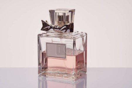 Photo pour Bouteille de parfum usagé pour femme sur fond gris avec réflexion - image libre de droit