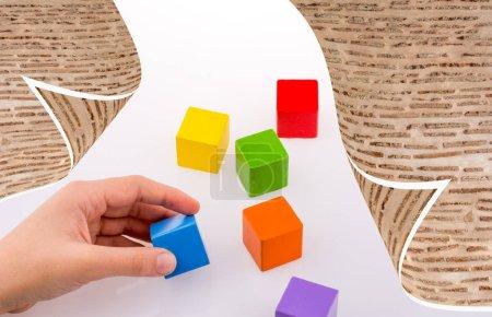 Photo pour Mains jouant avec des cubes colorés en arrière-plan - image libre de droit