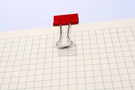Foto de Clip de papel coloreado en la página de cuaderno chequeado. - Imagen libre de derechos