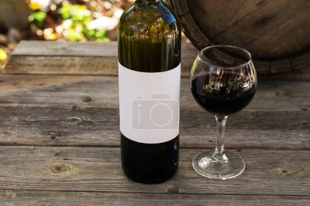 Photo for Red wine bottle and wine glass on wodden barrel - Royalty Free Image