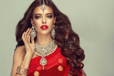 Photo pour Portrait de belle fille indienne de la mode. Jeune mannequin hindoue en bijoux kundan. Costume indien traditionnel, sari rouge  . - image libre de droit