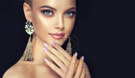 Beautiful model girl with  manicure on nails . Fashion makeup and cosmetics . Big golden shine earrings jewelry .
