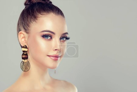 Beautiful model girl with  Fashion makeup and cosmetics . Big golden shine earrings jewelry .